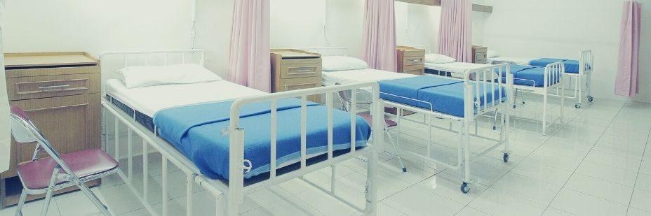 Chambre d'hopital avec plusieurs lits a la suite