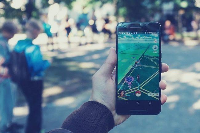 Une personne tien un téléphone dans les mains et joue a Pokemon GO.