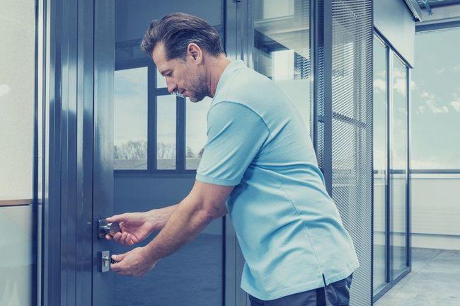 Un homme est entrain d'ouvrir une porte avec une clé.
