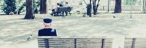 Une personne âgée est assise de dos sur un banc